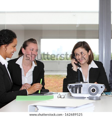Three successful businesswomen or partners in a meeting sitting together at a table smiling in satisfaction as one talks on the telephone watched by the others - stock photo