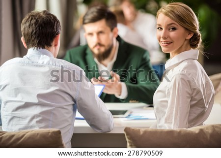 Three successful people sitting at the table in office and discussing project. - stock photo