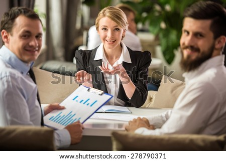 Three successful people sitting at the table in office and talking about business strategy. - stock photo