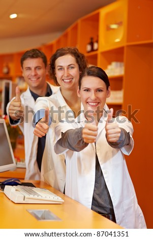 Three successful pharmacists in pharmacy holding thumbs up - stock photo