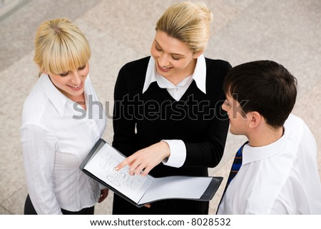 Three successful smiling people discussing a business project