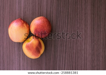 Three succulent red and yellow peaches over wood - stock photo