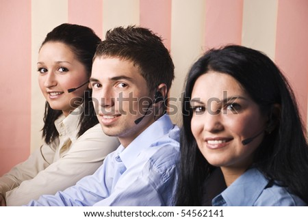 Three support operators people sitting at desk , looking you and smiling,focus on man