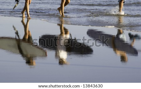 Three surfers rfleced in the beach and ready to jump in the water - stock photo
