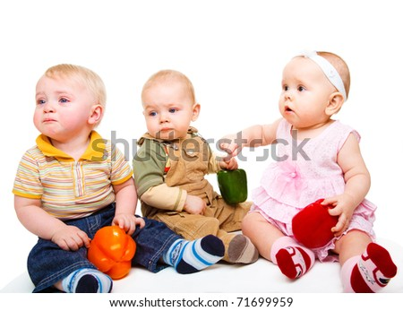 Three surprised baby friends holding ripe peppers - stock photo