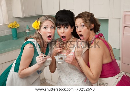 Three surprised middle-aged 1950s retro-style women with cigarettes and tea - stock photo