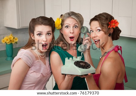 Three surprised women holding a rotary telephone in a kitchen - stock photo