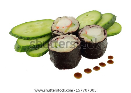 Three sushis with a crab and a cucumber, slices of a cucumber and drops of soy sauce on a white background - stock photo