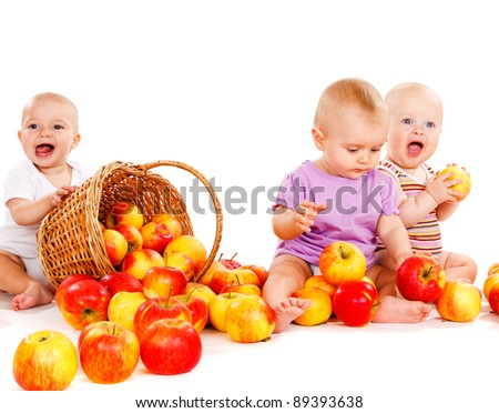 Three sweet cheerful babies playing with apples - stock photo