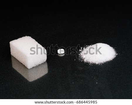 Three sweet sweetener options. White sugar cube, aspartame tablet and  artificial sweetener containing dextrose,fructose,sodium saccharin, acesulfame K. Low calorie healthy eating issue