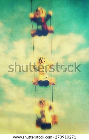 Three swinging clowns with motion blur, textured and retro filter - stock photo