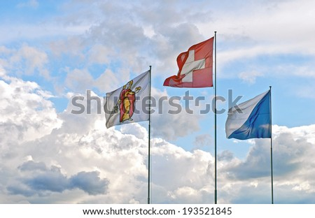 Three Swiss Flags: National Flag (Center), Flag of Zurich,(right) and Flag of the Patron Saint Verena (left) who joined the Theban Legion on its mission to Switzerland. - stock photo