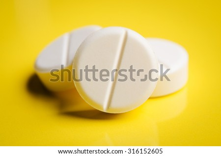 three tablets on yellow background - stock photo