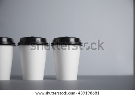 Three take away white paper cups with black caps on left side of image, isolated on simple gray background - stock photo