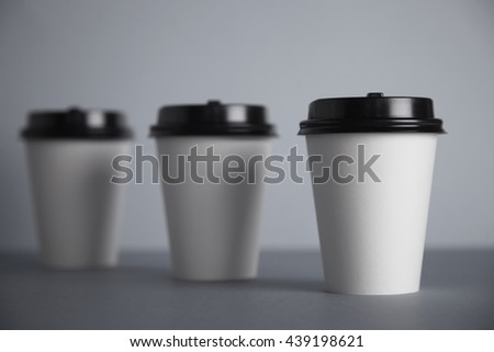 Three take away white paper cups with closed black caps, top view, isolated on simple gray background, first cup in close focus, cups behind are unfocused in bokeh - stock photo