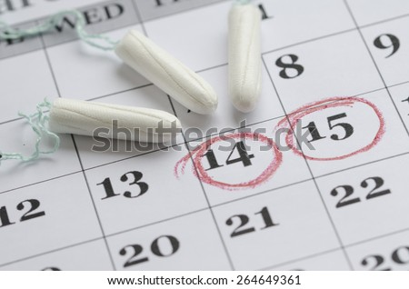 Three tampon laying on the menstruation calender