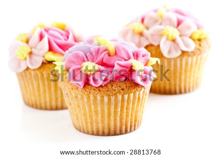 Three tasty cupcakes with icing flowers on white background - stock photo