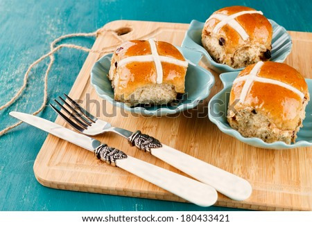 Three tasty Easter cross-buns served on chopping board on blue wooden background - stock photo