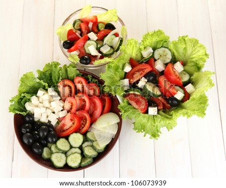 Three tasty Greek salad on white wooden background - stock photo