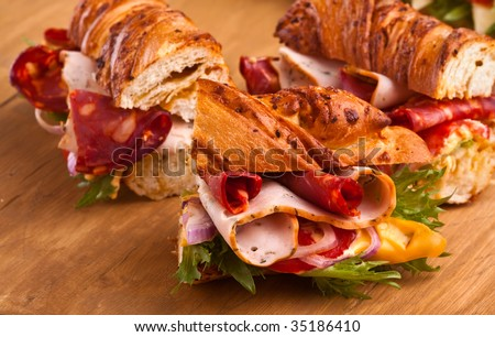 three tasty meat, cheese  and vegetables sandwiches - stock photo