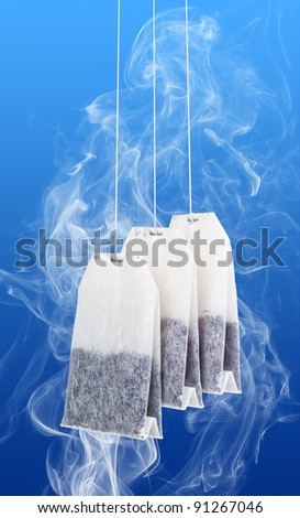 Three tea bags and steam in the blue background. Tea bags include paths for isolation from background. - stock photo