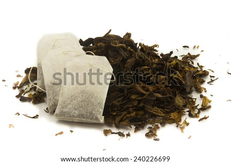 three tea bags over dried tea leaves background - stock photo