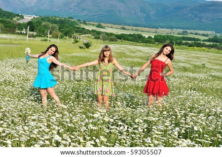 three teen girls walking together in the daisy field