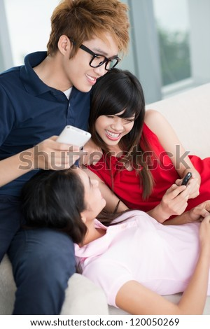 Three teenage friends communicating together at home
