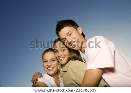 Three teenage friends hugging. - stock photo