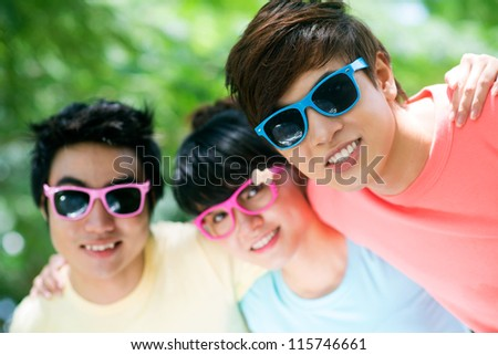 Three teenage friends in sunglasses embracing - stock photo