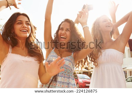 Three Teenage Girls Dancing Outdoors Against Sun