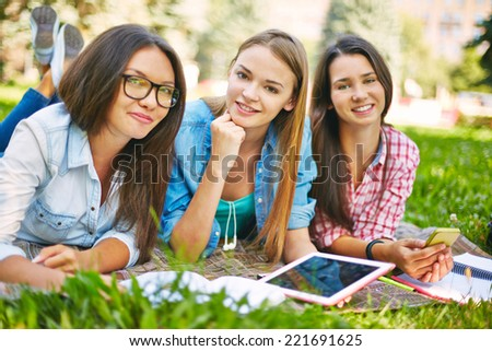 Three teenage girls lying in park on lawn - stock photo