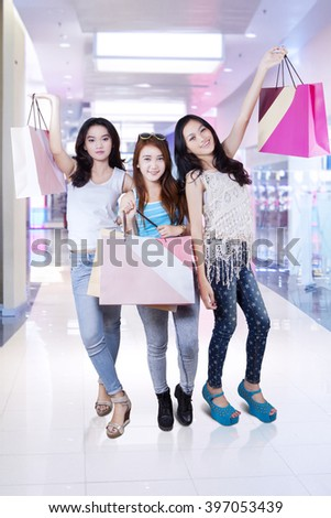 Three teenage girls smiling happy while holding shopping bags in the shopping center - stock photo