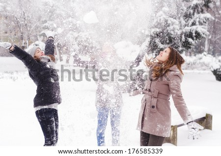 Three teenage girls throwing snow in the air on beautiful winter day. - stock photo