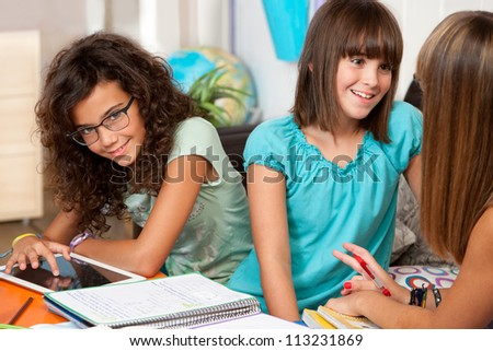Three teenage students discussing their homework at desk. - stock photo