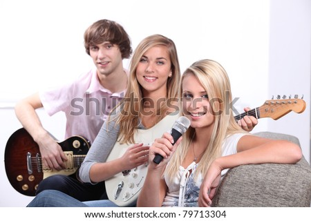Three teenager playing musical instruments - stock photo