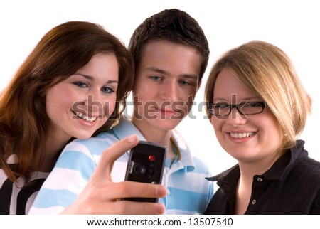 Three teenagers isolated. Boy on the middle is holding mobile phone and making the picture to the group. - stock photo