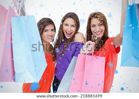 Three teenagers raising their arms while holding their purchases against snow falling - stock photo