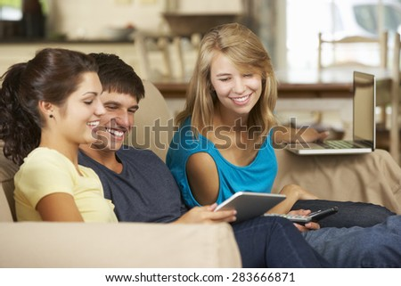 Three Teenagers Sitting On Sofa At Home Using Mobile Phone, Tablet Computer And Laptop - stock photo
