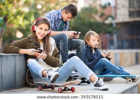 Three teenagers with smartphones in park outdoors - stock photo