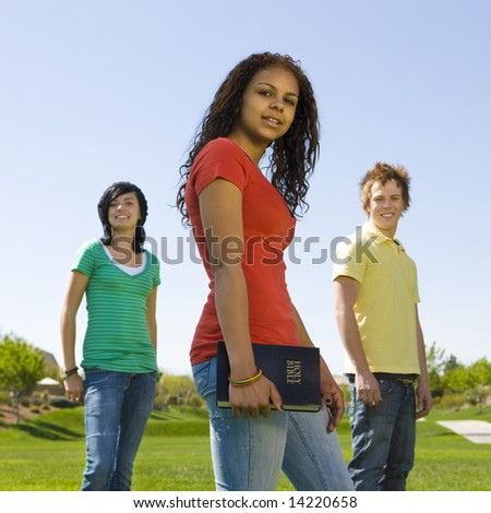 Three teens hang out at a park with a bible