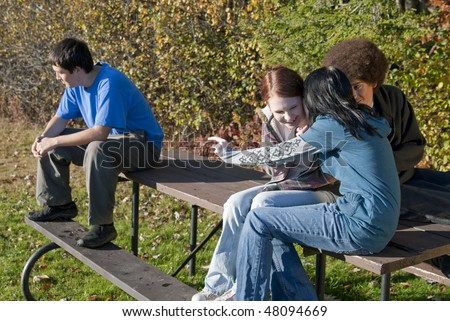 Three teens make fun of a mixed-race teen outdoors on a picnic bench - stock photo
