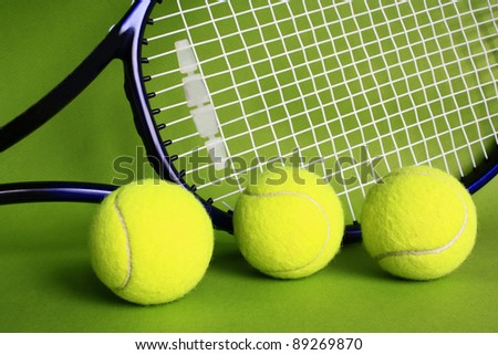 Three tennis balls and racket on green background. - stock photo