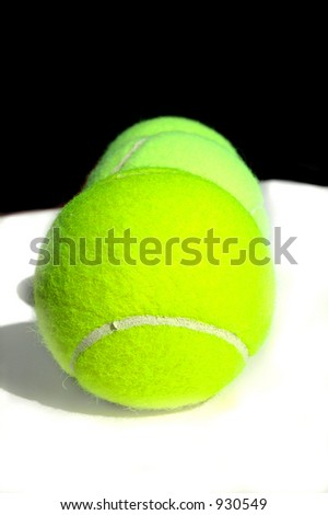 Three tennis balls in a line - stock photo