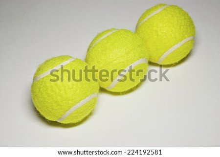 Three tennis balls in a row, close-up - stock photo