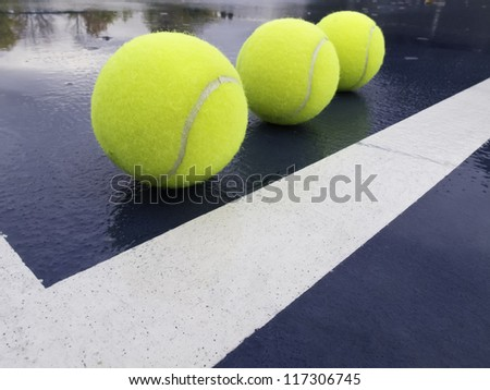 Three tennis balls in corner of a wet court after rain - stock photo