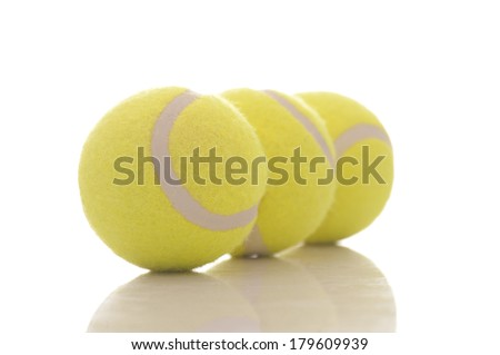 Three tennis balls isolated on white with focus on the first one.  - stock photo