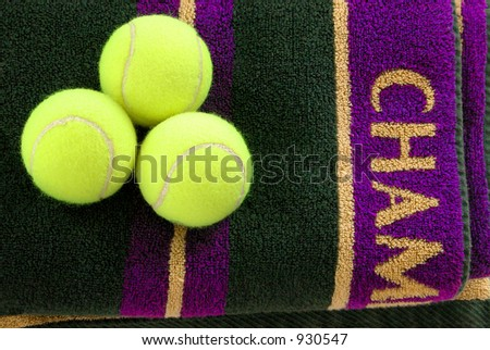 Three tennis balls on a purple and gold towel