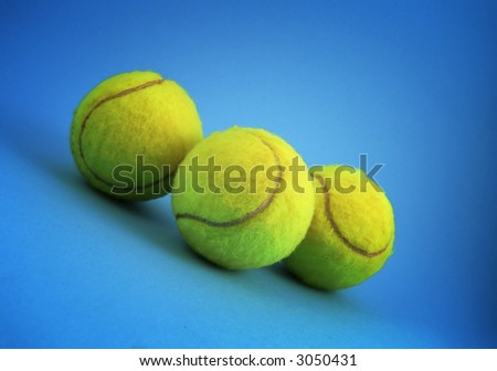 three tennis balls over blue background - stock photo