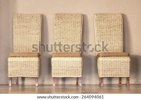 Three thatch chairs against rustic wall. Shot in Lesotho.